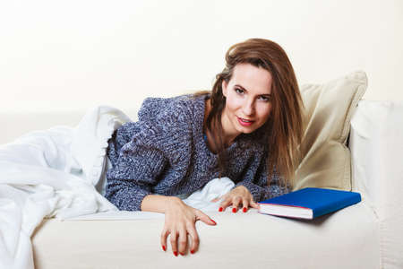 power nap: Beauty woman on sofa. Girl lying on couch with book relaxed or taking power nap after lunch.