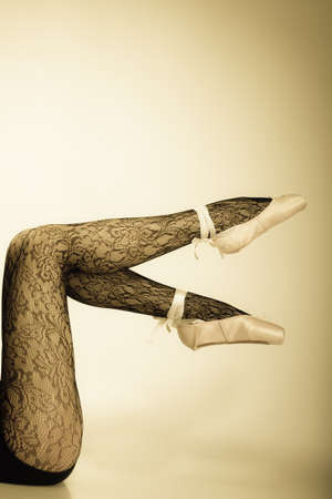 suppleness: beautiful woman ballet dancer, part of body legs in shoes and black lace tights studio shot vintage aged tone