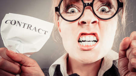 tearing: Business, documents and legal concept - Angry mad unhappy businesswoman holds crumpled contract Stock Photo