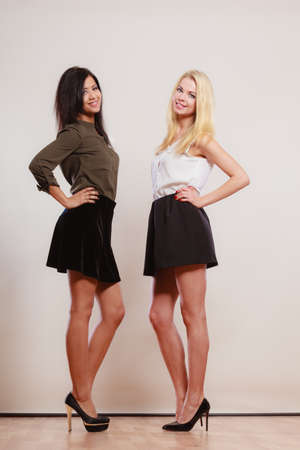 skirts: Two young women caucasian and african in trendy short black skirts posing in full length studio portrait on gray