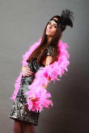 flapper: Mujer flapper retro en tiempo de carnaval. Femenino penacho de plumas de color rosa negro joven en el vestido de la cabeza y lentejuelas noche brillante Foto de archivo