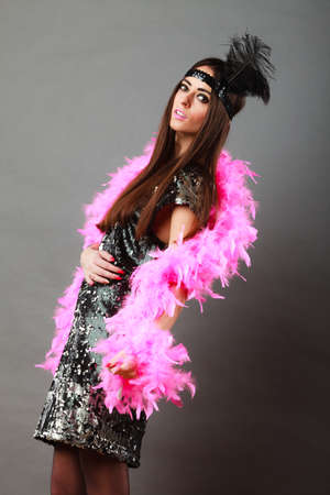 plume: Retro flapper woman on carnival time. Young female pink plume black feather on head and sequin glossy evening dress