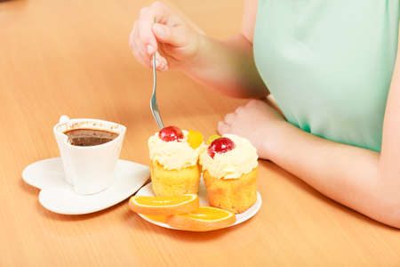 gula: Closeup of human hands with cup of coffee forking delicious gourmet sweet cream cake cupcake and orange. Appetite and gluttony concept. Foto de archivo