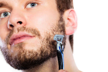 white beard: Health beauty and skin care concept. Closeup of male face. Young man guy styling beard holding disposable blue razor blade white background. Stock Photo