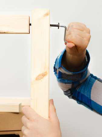 enthusiast: Human hand assembling wooden furniture using hex key. DIY enthusiast. Home improvement.