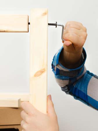 hex key: Human hand assembling wooden furniture using hex key. DIY enthusiast. Home improvement.