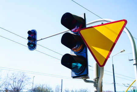 yield sign: Traffic lights and polish yield sign against sky background. Give way on crossroads. Stock Photo