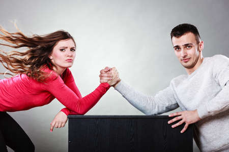 man arm: Partnership relationship concept. Girlfriend confronts his boyfriend. Woman and man arm wrestling challenge between young couple