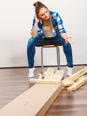 enthusiast: Worried helpless woman assembling wooden furniture. DIY enthusiast. Young girl doing home improvement. Stock Photo