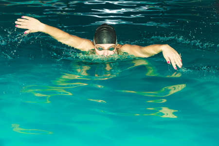 breath taking: Woman athlete swimming in pool. Active human swimmer taking breath. Water sport comptetition.