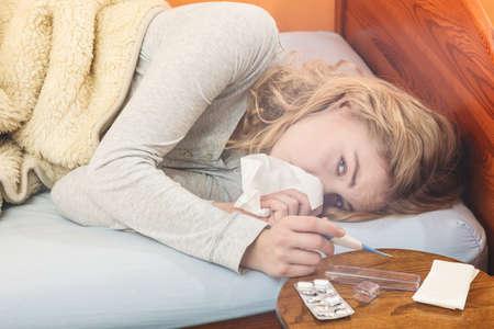 enfermos: Mujer enferma que pone en la cama bajo la manta de lana de estornudar en la celebraci�n de tejido term�metro. Muchacha enferma llam� gripe fr�o. Las p�ldoras y tabletas en la mesa.
