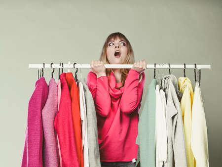 예쁜 여자는 옷장에 입을 옷을 재미 선택하는 데. 쇼핑몰 상점에서 화려한 젊은 여자 고객의 쇼핑. 패션 의류 판매 개념.