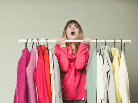 Jolie femme ayant du plaisir en choisissant des vêtements à porter dans la penderie. Superbe jeune shopping girl à la clientèle dans la boutique du centre commercial. Vente de vêtements concept de mode. Banque d'images