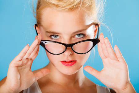 oculist: Optometrist, oculist and ophthalmologist concept. Young blonde woman with eyeglasses on blue background in studio. Stock Photo