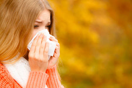 Flu cold, allergy symptom or other virus. Sick woman walking outdoor sneezing in tissue. Health care. Stock Photo