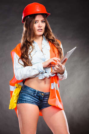 feminist: Sexy alluring woman structural engineer wearing helmet holding tablet computer. Strong girl feminist working in man profession. Independent female.