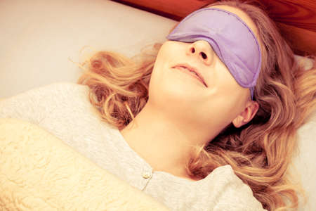 taking nap: Tired woman sleeping in bed wearing blindfold sleep mask. Young girl taking nap.    Stock Photo
