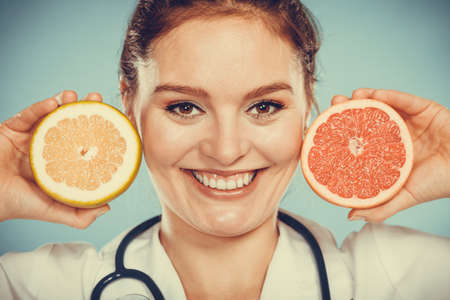 promoting: Happy dietitian nutritionist holding grapefruit having fun. Woman promoting healthy food fruit. Right eating nutrition and slimming concept.