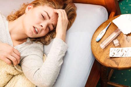 chory: Chora kobieta cierpi na ból głowy ból. Chora dziewczyna r w łóżku przeziębił. Termometr i tabletki na stole.