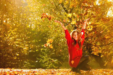 Happiness carefree. woman relaxing in autumn park throwing leaves up in the air with arms raised up. Beautiful girl in colorful forest foliage outdoor. Stock Photo
