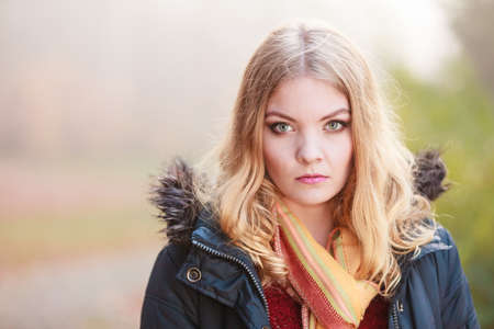 sad woman walking in fall forest park. Gorgeous blonde young girl in jacket. Autumn winter fashion. Bad emotion