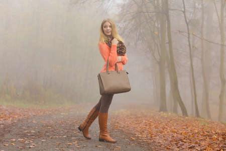 handbag: Fashionable woman posing in foggy autumn park. Pretty young girl in sweater pullover with handbag in forest. Fall fashion vogue.