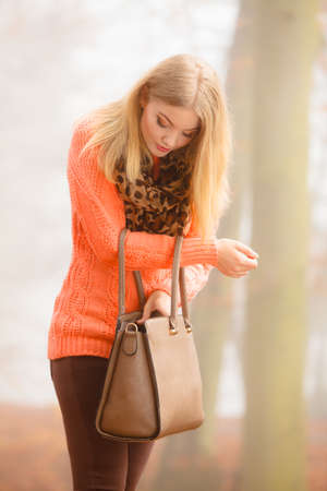 woman fashionable: Autumn fashion. Woman fashionable girl wearing vivid clothing holding brown leather bag handbag in hand, walking in autumnal foggy park, outdoors