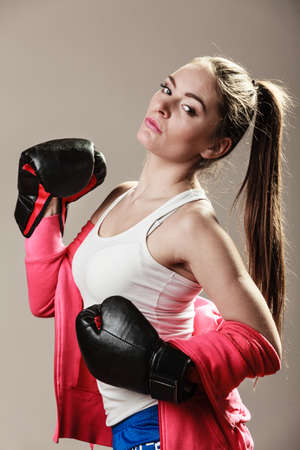 feministische: Feminist and emancipation idea. Woman in male occupation, training, boxing. Fit female fitness girl doing exercise on grey background.
