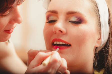 visagiste: Make up artist applying lipstick with brush on pretty gorgeous woman lips. Closeup of visagiste and young girl. Beauty and makeup concept. Stock Photo