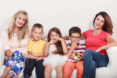 woman on couch: Happy family. Mothers women and kids little girl and boys sitting at sofa couch at home.