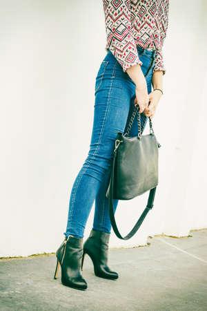 mezclilla: Traje de moda de otoño. La mujer de moda piernas largas con pantalones de mezclilla negro elegantes zapatos de tacones altos y bolso al aire libre en la calle de la ciudad Foto de archivo