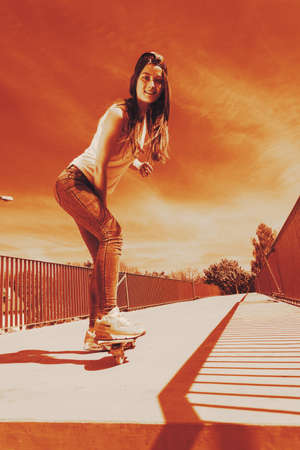 summer sport: Summer sport and active lifestyle. Cool teenage girl skater riding skateboard on the street by sunset. Outdoor.