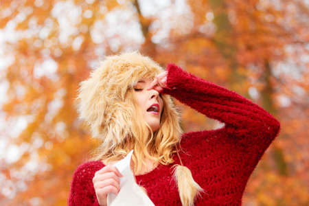 Sick ill young woman girl in fall autumn forest park sneezing into tissue.