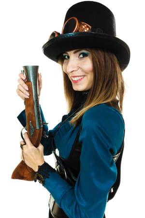 finger on trigger: Smiling young steampunk islolated girl on white holding fancy rifle with finger touching trigger. Fantasy old fashion wearing hat and goggle.