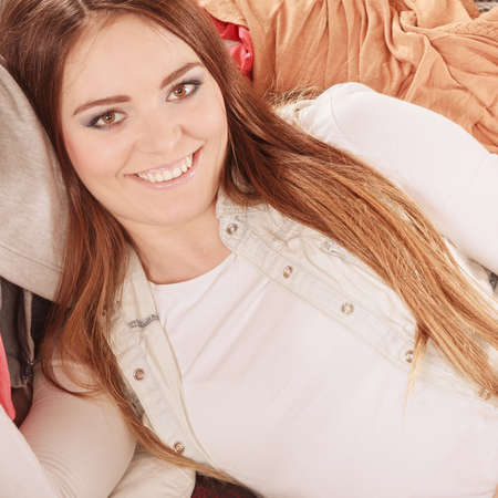 disorganized: Portrait of happy glad young woman girl lying on stack of clothes. Disorder and mess.