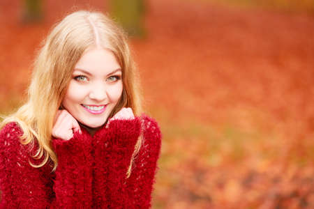 fall winter: Portrait of stunning pretty smiling fashionable woman in fall forest park. Happy gorgeous young girl in maroon sweater pullover. Autumn winter fashion. Stock Photo