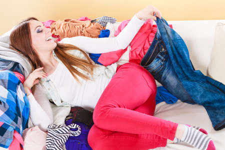messy room: Happy woman lying on sofa couch in messy living room. Young girl surrounded by many stack of clothes. Disorder and mess at home. Stock Photo