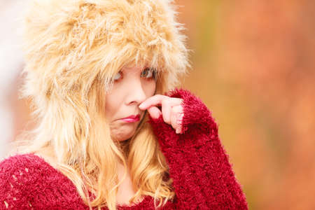 shivering: Portrait of pretty fashionable woman in fall forest park feeling cold. Gorgeous young girl in fur winter hat and sweater shivering. Autumn fashion.