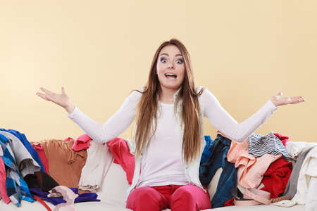 Helpless woman sitting on sofa couch in messy living room shrugging. Young girl surrounded by many stack of clothes. Disorder and mess at home. Banque d'images