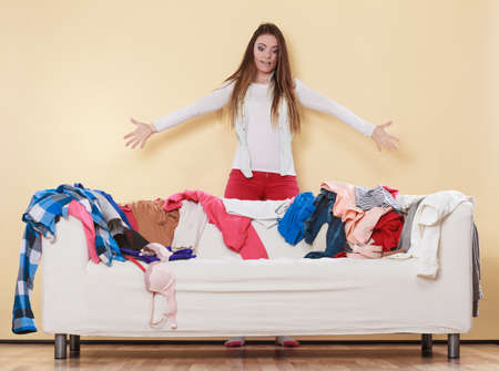 pile of clothes: Desperate helpless freaking out woman standing behind sofa couch in messy living room. Young girl surrounded by many stack of clothes. Disorder and mess at home.