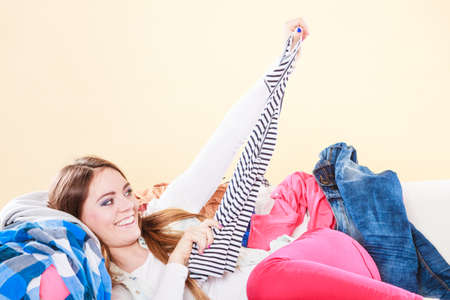 living things: Happy woman lying on sofa couch in messy living room. Young girl surrounded by many stack of clothes. Disorder and mess at home. Stock Photo