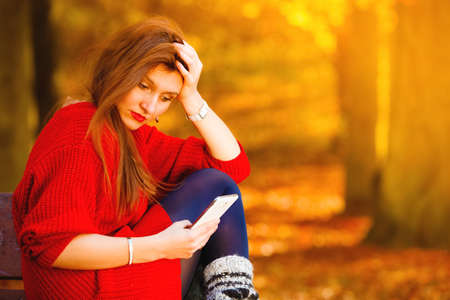 sad: Communication technology. Sad upset girl unhappy woman sitting on bench in autumn park with mobile phone smartphone, reading sms Stock Photo