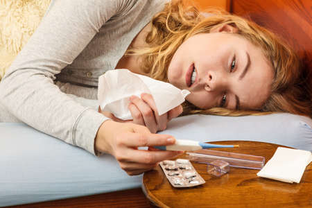 Sick woman laying in bed under wool blanket holding thermometer and tissue. Ill girl caught cold flu. Pills and tablets on table.