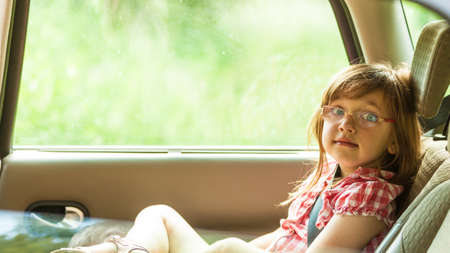 fastened: Little girl child kid in glasses with seat belt fastened sitting in car. Holidays vacation trip. Safe summer travel.
