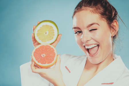 Happy dietitian nutritionist holding grapefruit having fun. Woman promoting healthy food fruit. Right eating nutrition and slimming concept.  Stock Photo