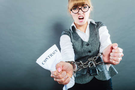 chained: Business and stress concept. Furious businesswoman in glasses with chained hands holding contract grunge background Stock Photo