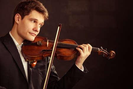 fiddler: Art and artist. Young elegant man violinist fiddler playing violin on black. Classical music. Studio shot.
