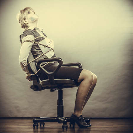 bound woman: Afraid businesswoman bound by contract terms and conditions with mouth taped shut. Scared woman tied to chair become slave. Business and law concept.