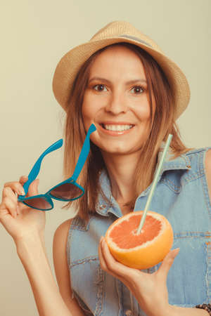 flirty: Happy glad woman tourist in straw hat holding sunglasses and grapefruit citrus fruit. Seductive and flirty girl. Healthy diet food. Summer vacation holidays concept.