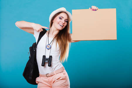 hitchhiking: Summer tourism active lifestyle concept. Woman happy female tourist hitchhiking with blank sign cardboard on blue